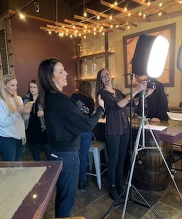 Ariana Goffe taking photographs at a Timeless Skin Solutions event.